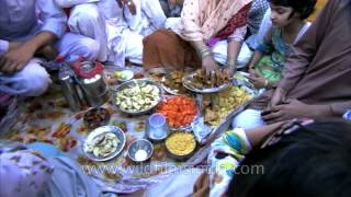 Indian Muslim family place food items on plates during Iftar