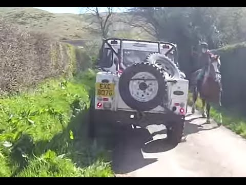 A group of 4x4 Land Rovers meeting horse riders in Shropshire