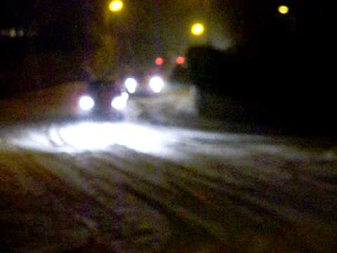 CARS DRIVING DOWN A SNOWY ROAD
