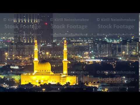Dubai skyline with The Jumeirah Mosque illuminated at night timelapse. Dubai, United Arab Emirates