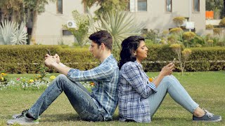 Couple sitting in a park with back towards each other using mobile phones