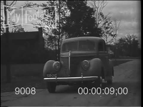 1938 Ford V-8 Deluxe Sedan Automobile Driving in Suburbia