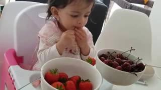 Baby eating cherries and strawberries