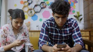 Excited Indian girl showing mobile phone messages to her boyfriend, but he ignores her