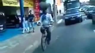 هندي يقود دراجة حاملاً على رأسه أنبوبة غاز وبطيخة