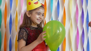 Happy little girls having fun by bursting balloon at a birthday party - Surprised and Scared