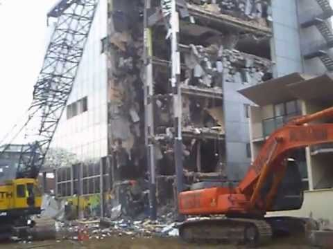 excavator and crane with wrecking ball demolishing