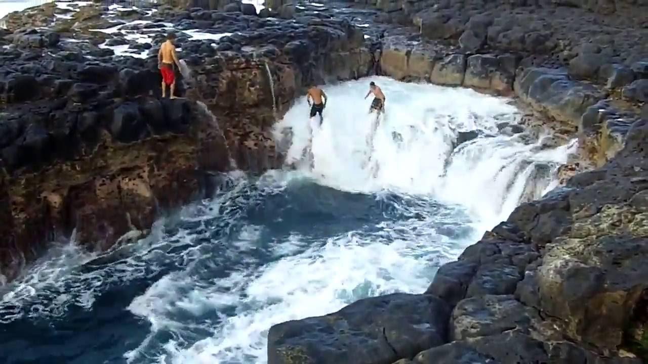 """Les ones del mar poden ser perilloses però segur que no tant com les que es produeixen en la """"piscina de la mort"""" a Queen 's Bath, una piscina de marees única a l'illa de Kaua'i (Hawaii). La temeritat d'aquests joves va poder costar-los la vida ... de fet ja han estat diverses les persones mortes en aquest lloc. Té una gran bellesa natural i pot semblar molt tranquil·la, però pot esdevenir un lloc extremadament perillós en tan sols uns segons."""