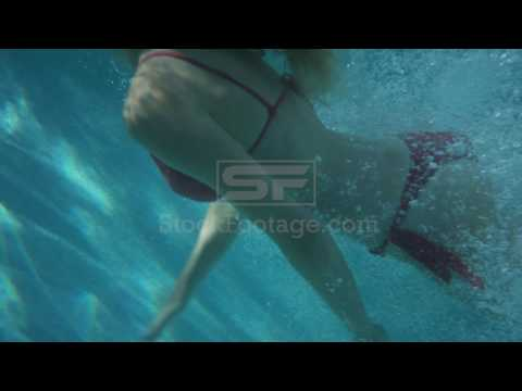 Medium slow motion tracking shot of woman diving into pool