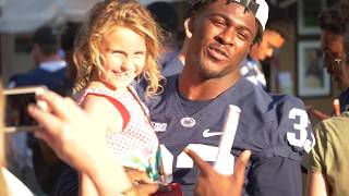 Penn State football players hit the streets to hand out posters