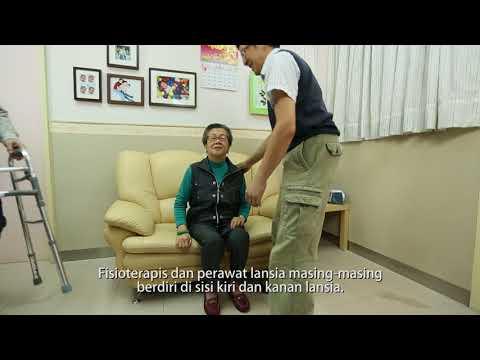 2 orang membantu lansia berdiri dari posisi duduk