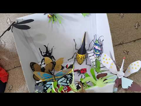 Summer and children playing with paper sculptures of insects