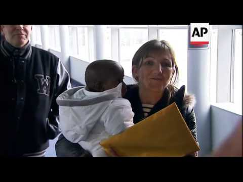 Parents return with their adopted children from Haiti