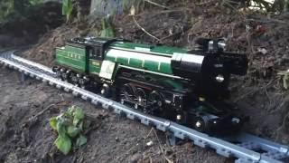 Kereta api mainan yang menembus rumah dan halaman.