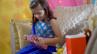 Excited cute Indian girl opening her rakhi gift