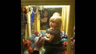Little girl in a ball claw machine