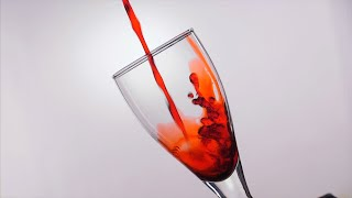 Slow motion shot of pouring red wine into a glass