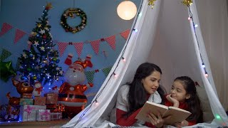 Indian mother and daughter reading storybook together in the tent on Christmas holiday