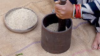 An Indian woman pounding bajra / pearl millet with iron mortar and pestle