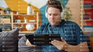 Serious guy wearing headphones using tablet touching gadget screen at home