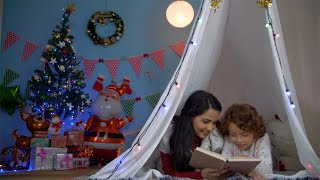 Happy Indian mother reading a storybook to his little son at night - Christmas fun