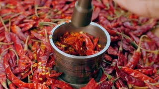 Chef crushing red chili flakes in metal mortar and pestle