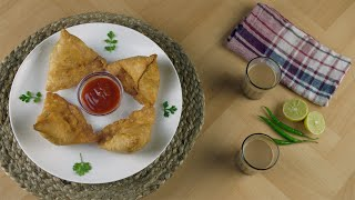 Top view of beautifully plated samosas with a bowl of tomato sauce - Indian street food