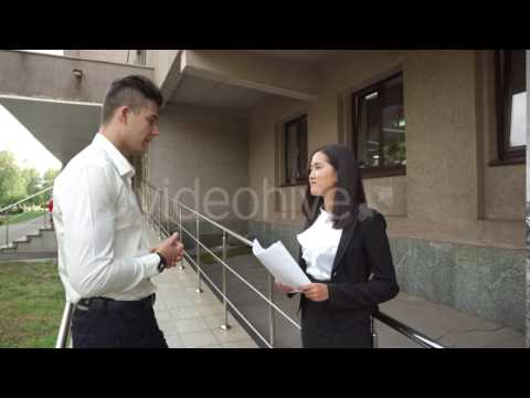 Young Beautiful Asian Business Woman Female and Caucasian Male Look at Documents Talk on Office