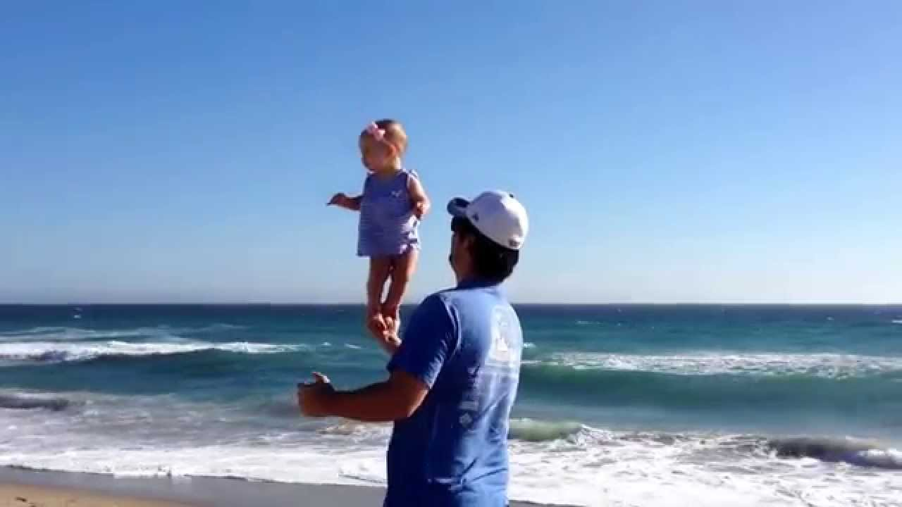 Balancing Baby Little Girl Stands In Dad S Hands At The