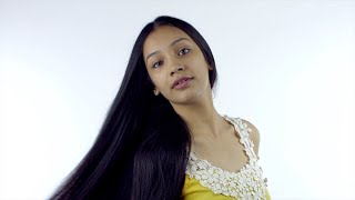 Portrait of a pretty Indian girl tossing her long hair and posing towards the camera