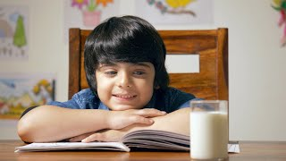 Indian boy reading a school book - Caring mother gives him milk. Study and Homework