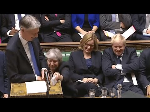 Theresa May hands cough sweets to Philip Hammond during budget speech