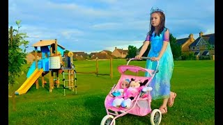 Little Girl with Baby Doll in Pink Stroller Playing at the Playground
