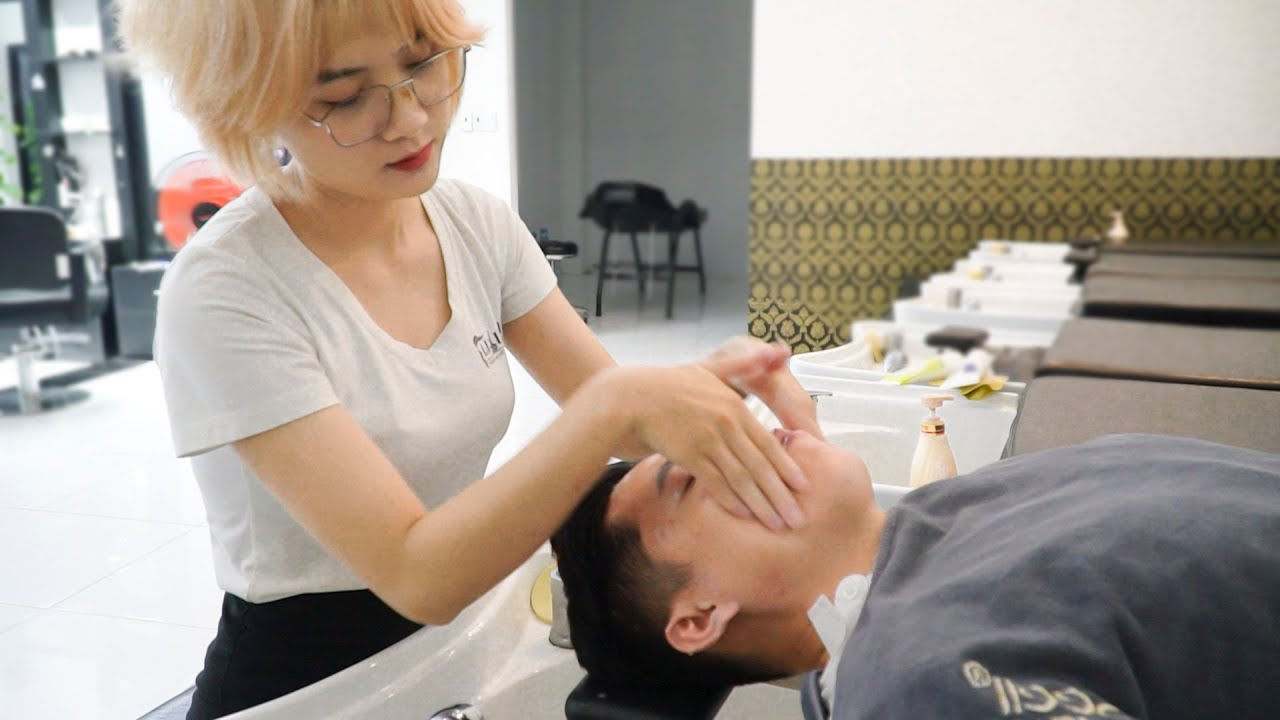 Lovely blonde, young vietnamese girl shampooing and relaxing face massage in Asia's most classy