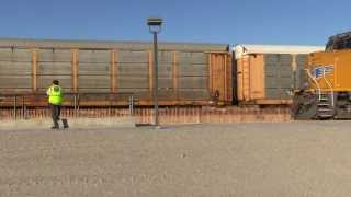 Eastbound Union Pacific Autorack Train Running In The Shadows Of A Wind Turbine