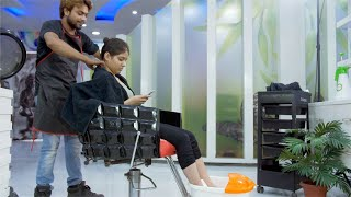 Pretty Indian girl using her smartphone while sitting on a chair at a beauty salon