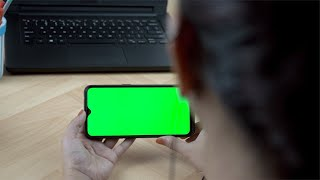 Pan shot of an Indian girl watching a video/movie on her green screen mobile