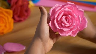 A woman arranging artificial petals of a big pink rose