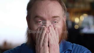 Man covering his face and eyes with his hands