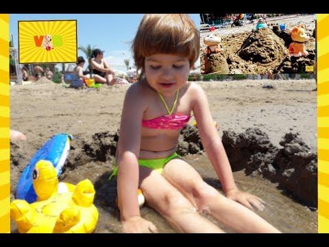 На пляже. Дети строят замок из песка.