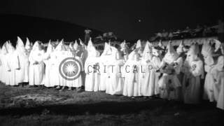 Ku Klux Klan members dressed in white robes stand in a circle during ceremonies i...HD Stock Footage