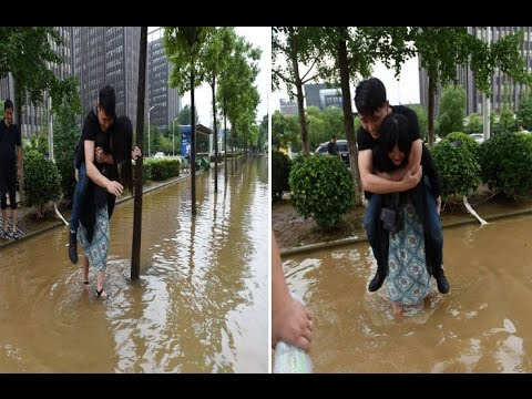 Woman carries boyfriend on her back while crossing a flooded street so he won't ruin his shoes