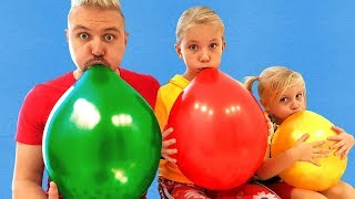 Kids and dad playing with Huge Colored Balloons