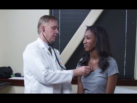 Doctor examining young woman's heart rate, reviewing personal health record