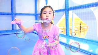 Boram joue dans une aire de jeux intérieure avec un jouet bulle de savon