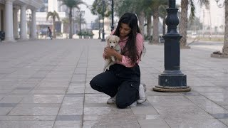 Young beautiful girl playing with her cute puppy in the streets of an Indian market
