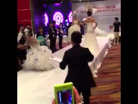 Model in wedding dress falls down during a Chinese bridal fashion show