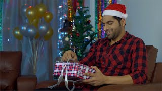 Handsome young man opens his gift box while sitting near a decorated Christmas tree
