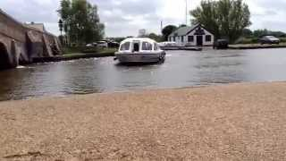 Watching boats going under Potter Heigham Bridge, in the heart of the Norfolk Broads. Uk