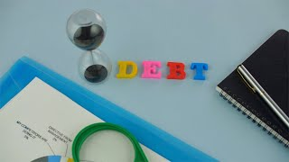 "Pan shot of the word ""Debt"" written with colorful plastic letters on a blue platform"